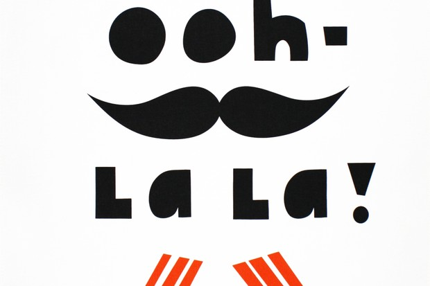 A white tea towel with black with that says Ooh La La. There is a black moustache on the tea towel