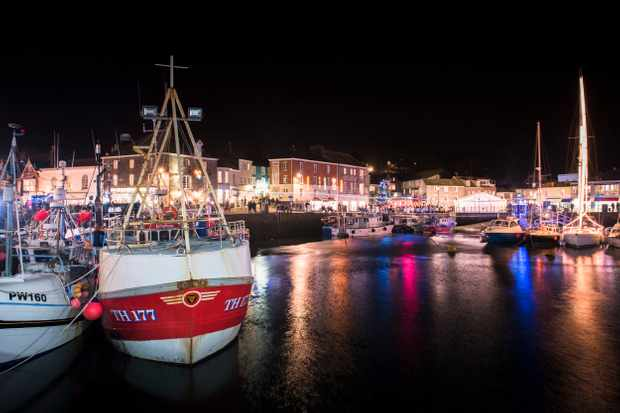 Padstow harbour during the Christmas festival. The harbour has a couple of boats in it with houses in the background. The water in the harbour is glistening with red and blue lights reflected in it