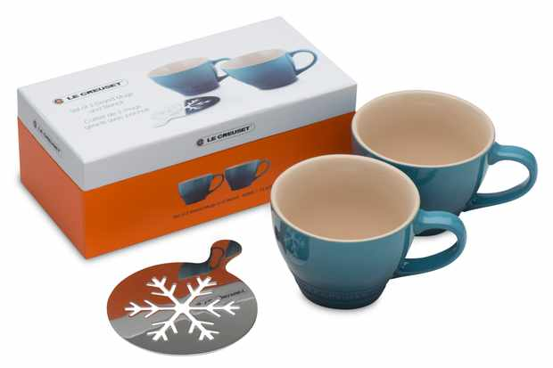 Two mugs in the colour way marine with a metal snowflake stencil next to the mugs