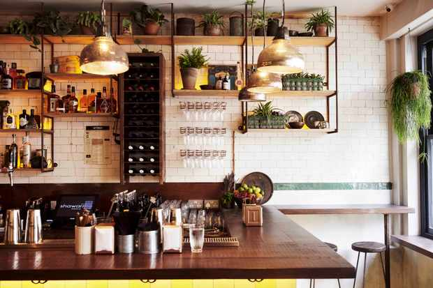 A wooden bar with shelves behind lines with bottles of spirits and a wine rack