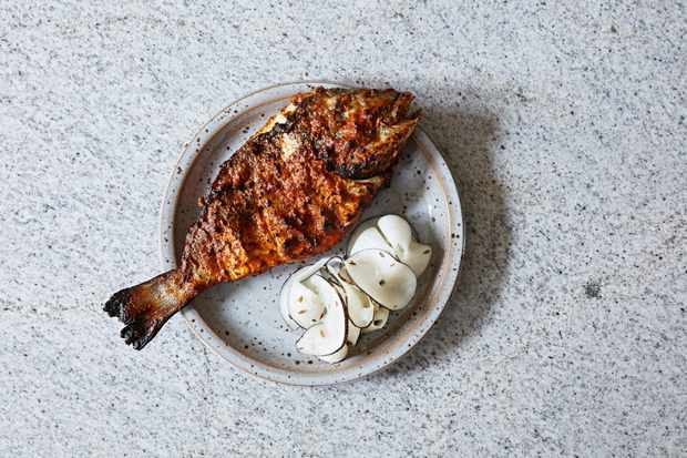 A grilled fish on a white plate