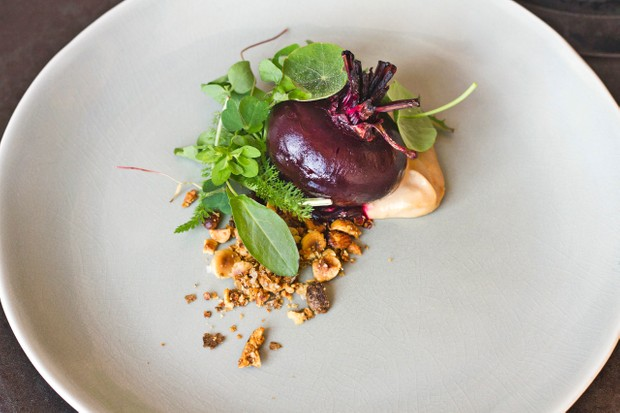 Where the Light Gets In, Stockport. Round light grey plate of a whole beetroot, hazelnuts and leaves