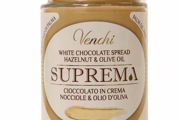 A jar of Venchi white chocolate spread with hazelnut and olive oil. The jar of spread has a gold lid and a white label with writing on it