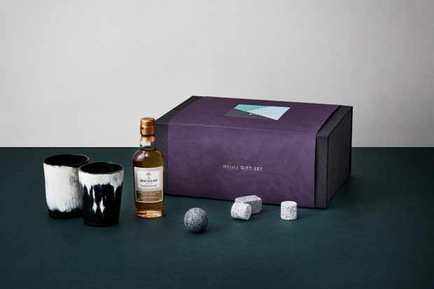 A purple box with a small bottle of whisky, a tot and whisky stones laid out next to it
