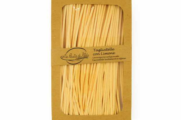 A brown box with a clear front, it is filled with long strands of yellow tagliatelle