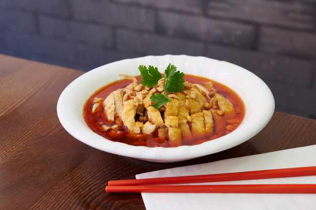 A bowl of chicken with red chilli sauce and red chopsticks at Baiwei Restaurant Chinatown