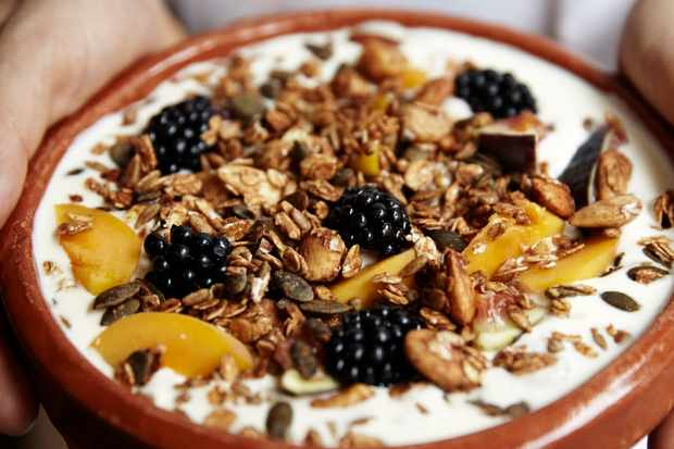 A terracotta ramekin filled with granola, yogurt and blackberries