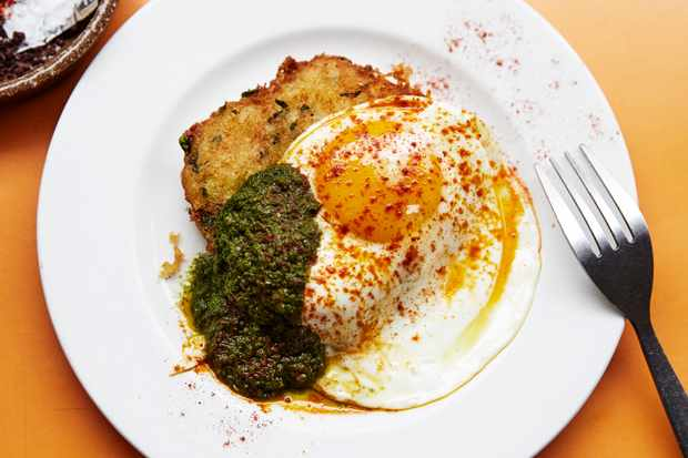 A plate with a fried egg on top of a fish cake with green pesto