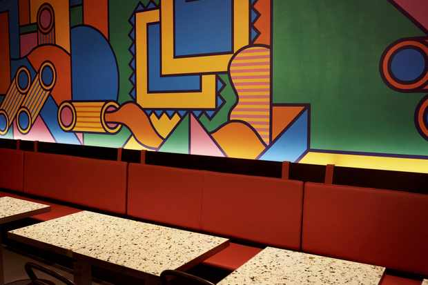 Tables next to a wall with a colourful mural