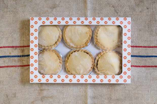 A packet of six Hobb's House Bakery mince pies on a striped tea towel