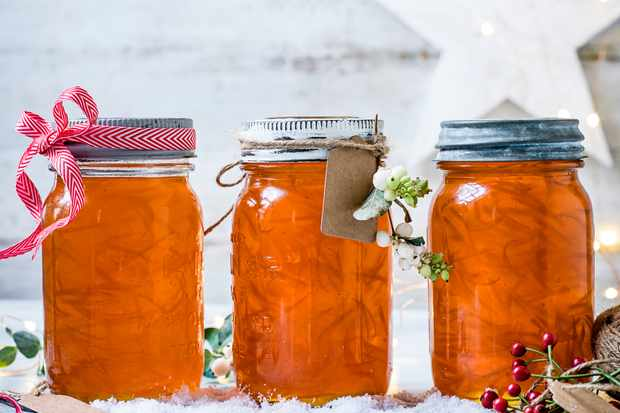 Three jars of orange Aperol marmalade with ribbon round the top