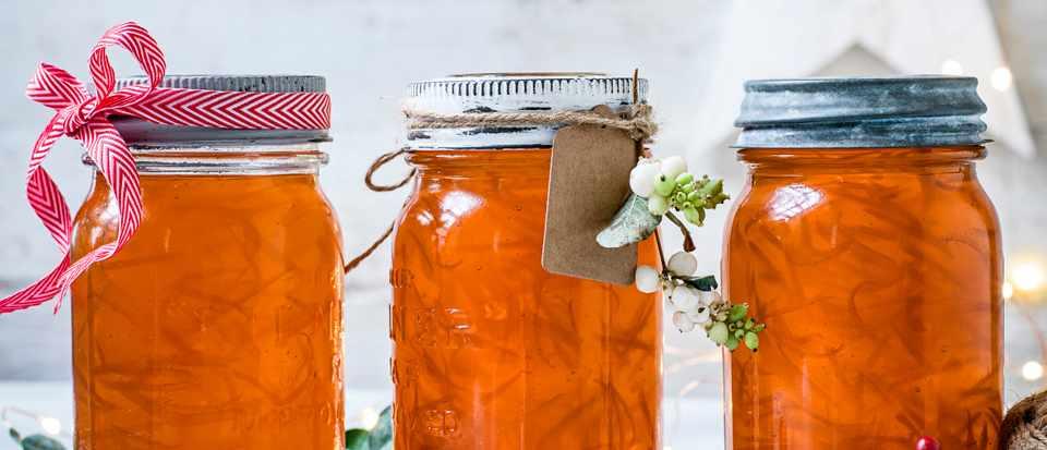 Three jars of orange Aperol marmalade with ribbon round the top