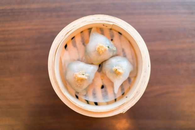 Bamboo steamer filled with three clear shrimp dumplings