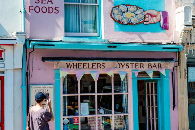 A woman uses her phone to photograph the famous Wheelers Oyster Bar established in 1856, Whitstable, Kent, UK
