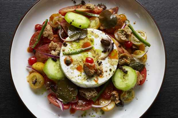 A white bowl filled with a Greek salad topped with a big circle of feta cheese
