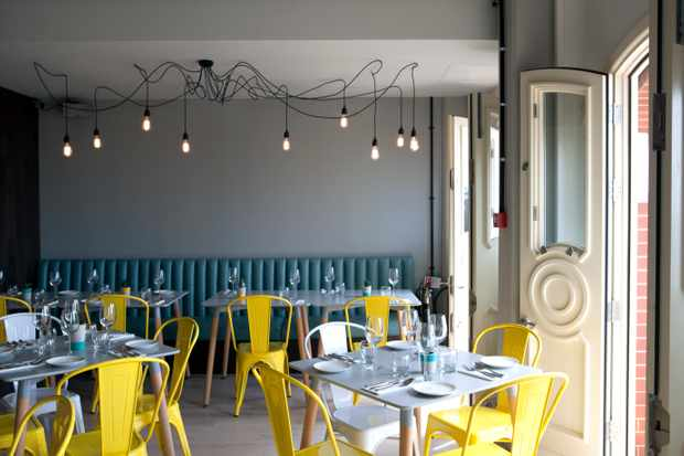 A room with wooden tables, yellow metal chairs and blue banquette