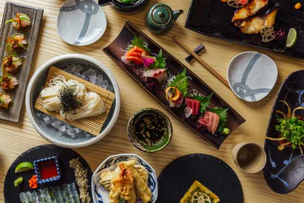 A table laden with plates of Japanese food