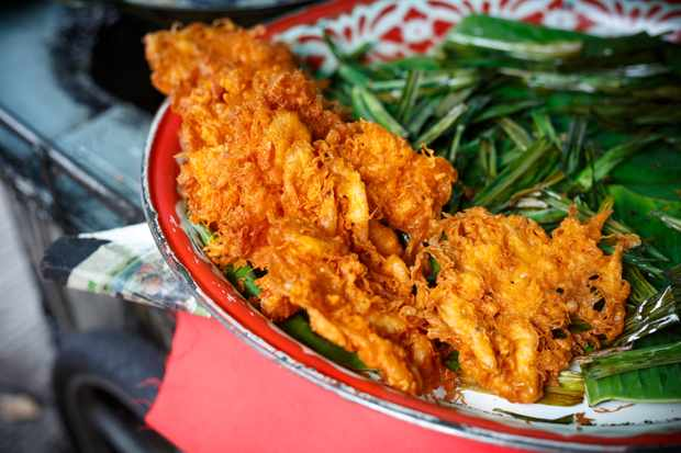 A bowl of deep fried prawns in batter with some green veg on the side