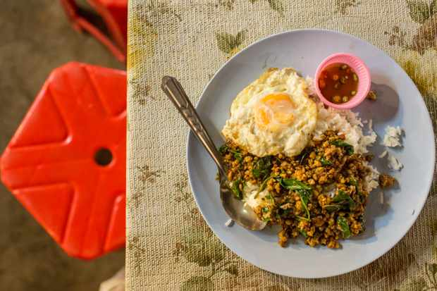 plate with stir fried chicken, fried egg and chilli dipping sauce