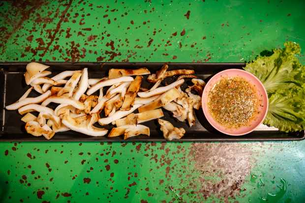 Sliced chargrilled squid onn platter with bowl of dipping sauce