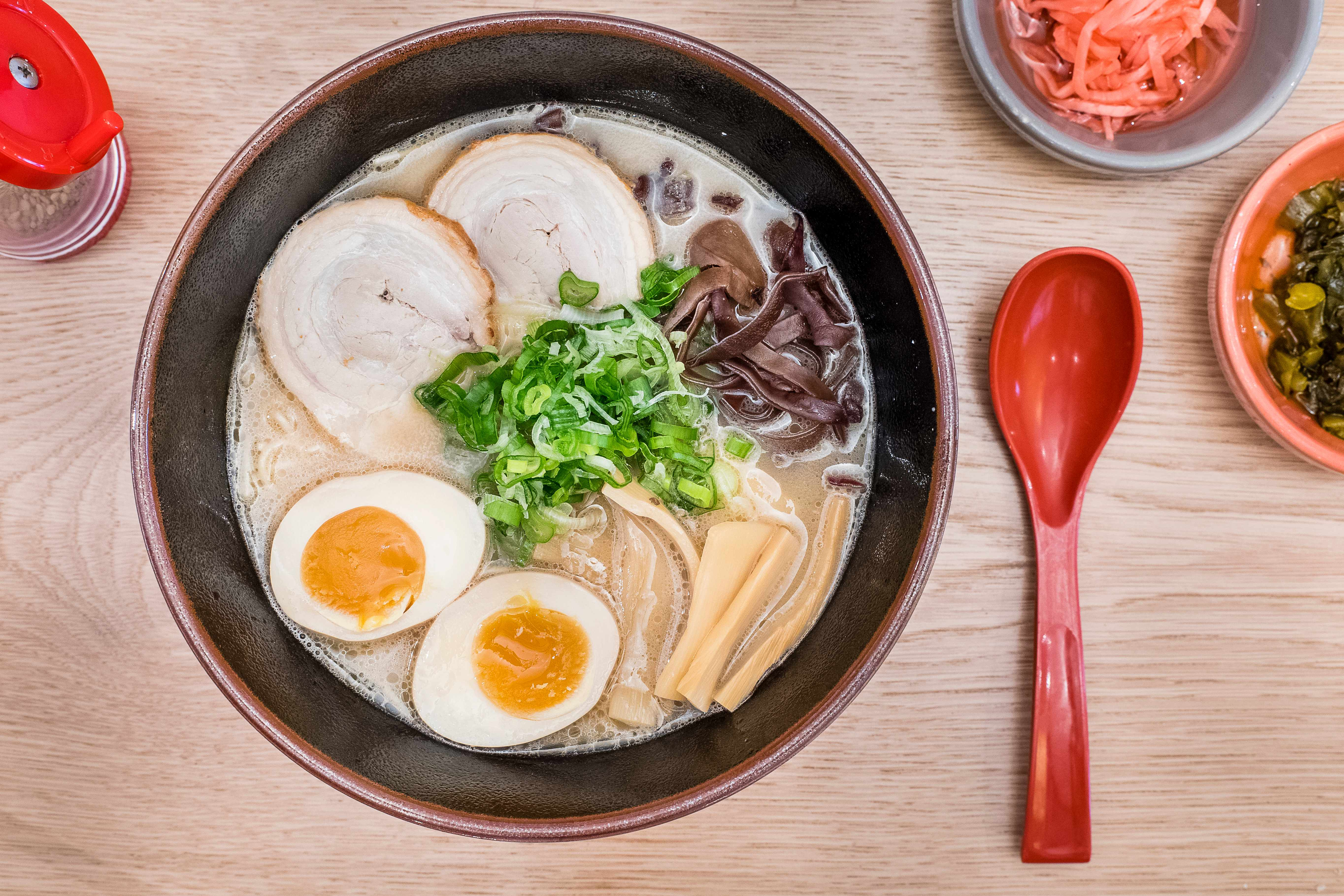 Bowl of ramen with two eggs and pork in, with a red plastic spoon on the side