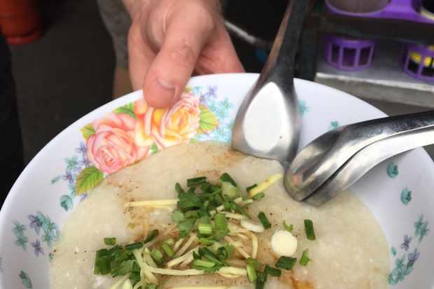 Bowl with rice porridge, ginger, spring onion topping