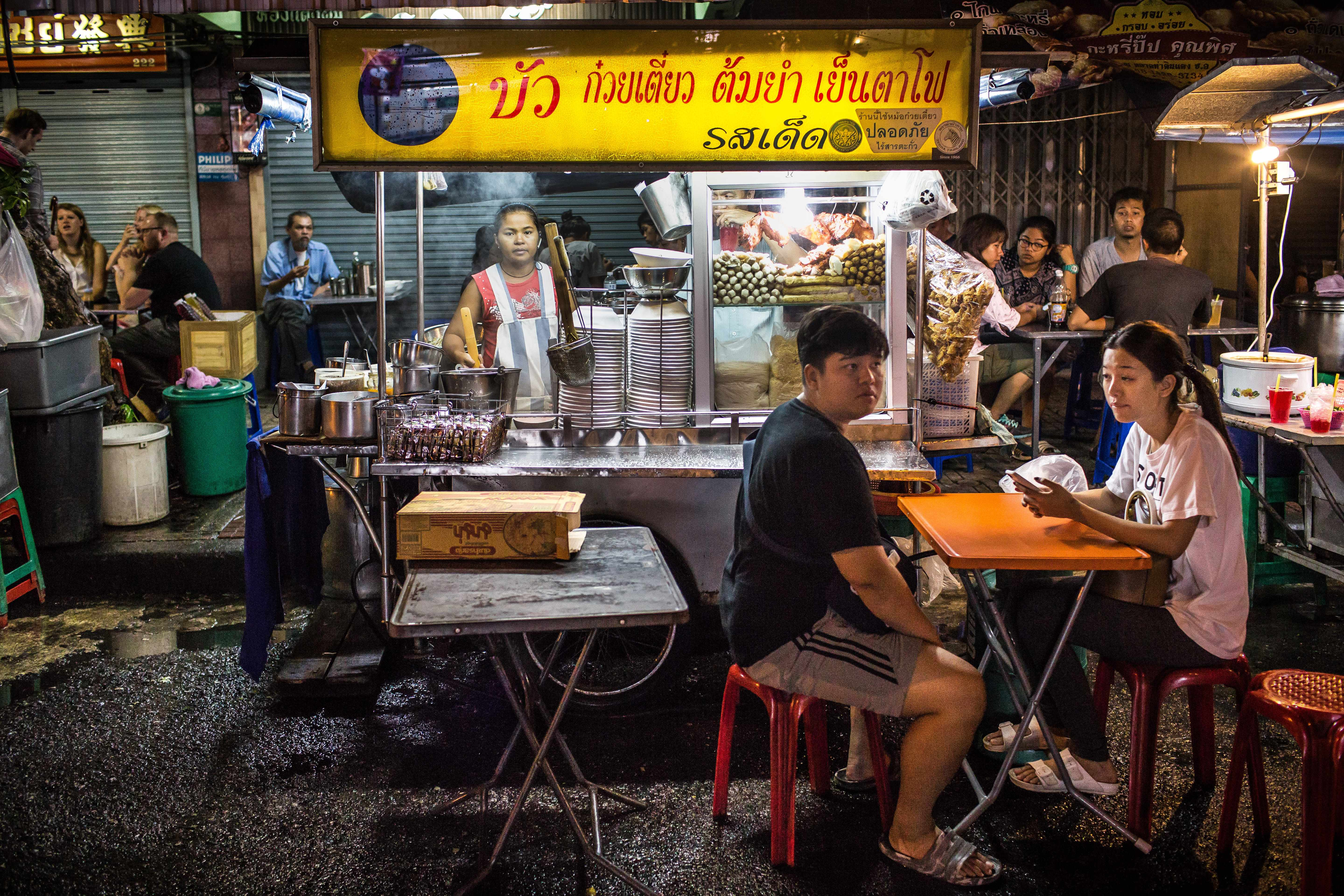 Bangkok Food Guide - Street food scene with woman standing behind stall