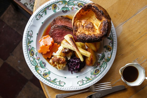 A roast dinner with beef, yorkshire puddings and vegetables