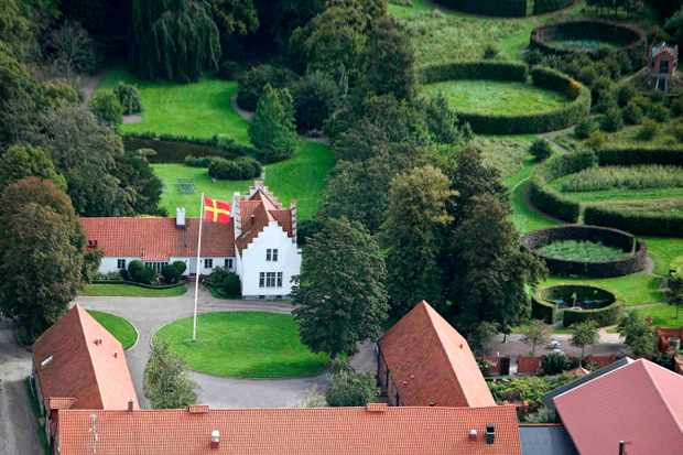 Aerial shot of a red-roofed hotel with green fields