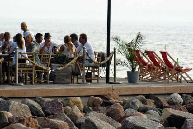 People sat on seaside terrace at Sillen and Makrillen restaurant