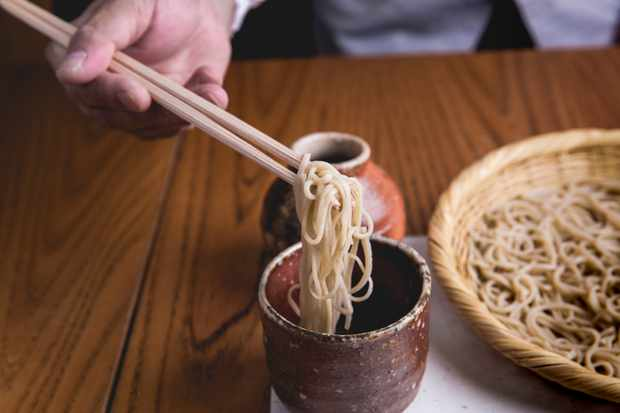A hand dipping noodles into a pot of sauce on a wooden table