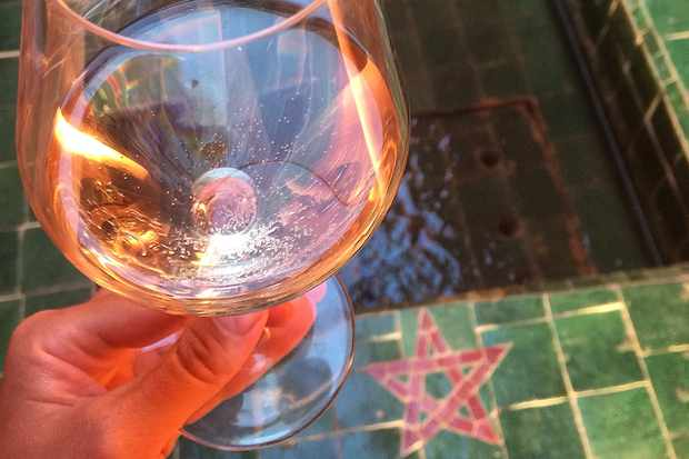 Glass of rose wine against some green tiles