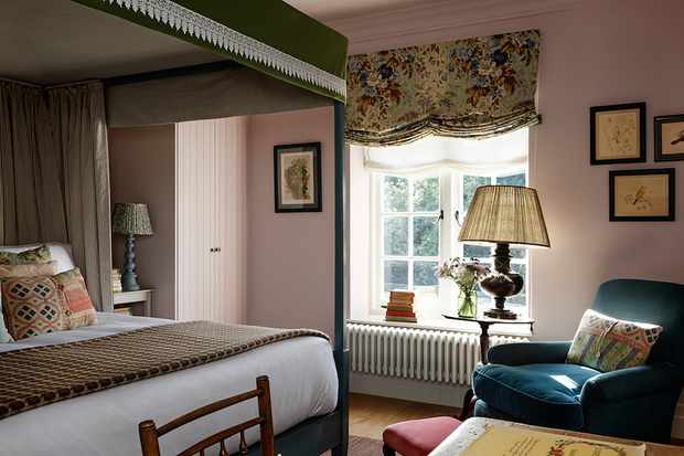 A bedroom with a four-poster bed, lamp and window with a blind