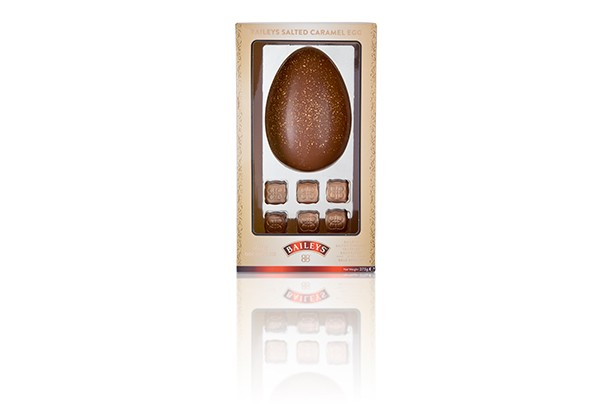 An Easter egg with glitter on the front is packaged in a plastic box. There are six truffles below the egg