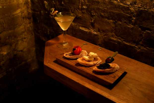 A martini and a wooden plater with three open sandwiches