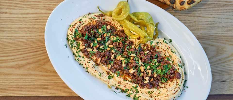 Baharat-spiced lamb, hummus, pine nuts, raisins and flatbreads