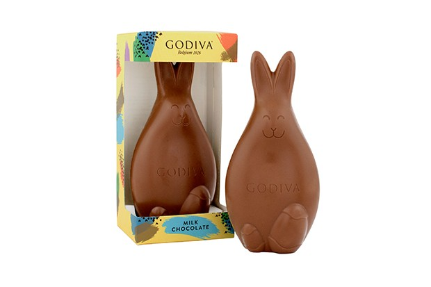A milk chocolate bunny is sat outside its box next to a box with a bunny on the inside