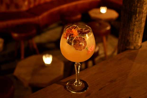 A large wine glass filled with orange-coloured liquid