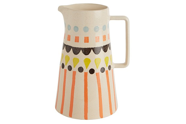 A cream jug with hand-sponged colourful print design in orange, yellow, black and blue