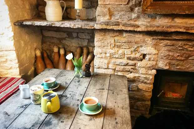 Cup of tea by the fire at The Potting Shed Crudwell