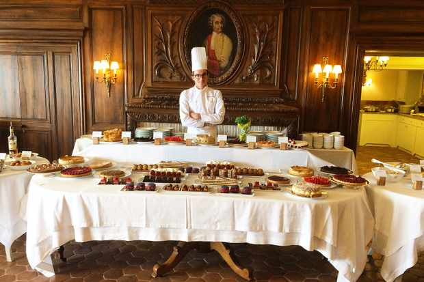 A chef standing behind a large table filled with desserts