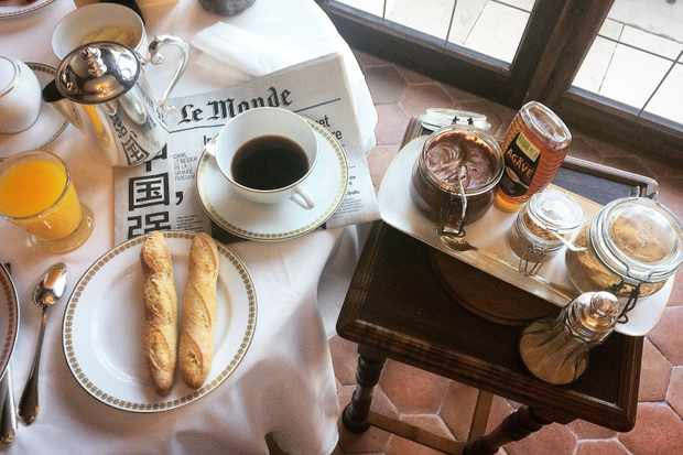 A breakfast table with baguettes, coffee and chocolate spread