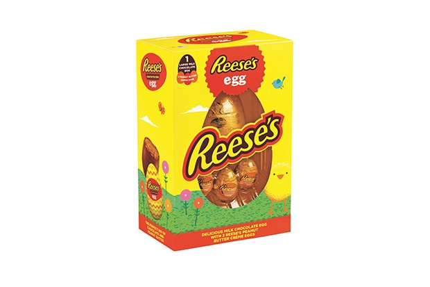 A bright yellow box with Reese's written on it has an egg wrapped in gold foil on the inside. Below it are three small peanut butter eggs