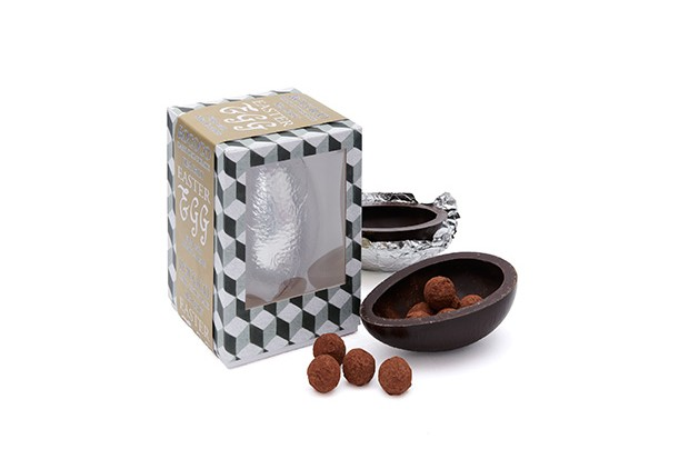 A blue and white graphic box is filled with an egg wrapped in silver foil. There is half an egg open on the outside with truffles inside