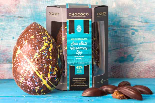 A milk chocolate Easter egg with a colourful splash design on the egg. Its box is sat next to it with dark chocolate cocoa pod truffles to the side with caramel pouring out of them
