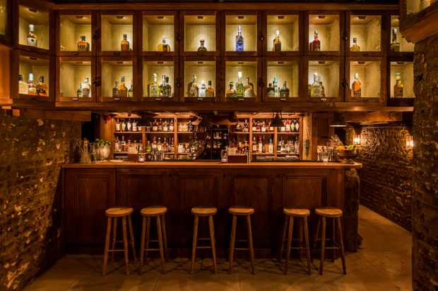 A wooden bar with cabinets full of bottles
