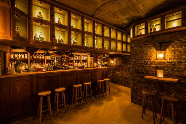 A wooden bar with bare brick walls