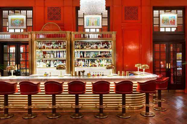 A room with red walls and a long bar with chairs