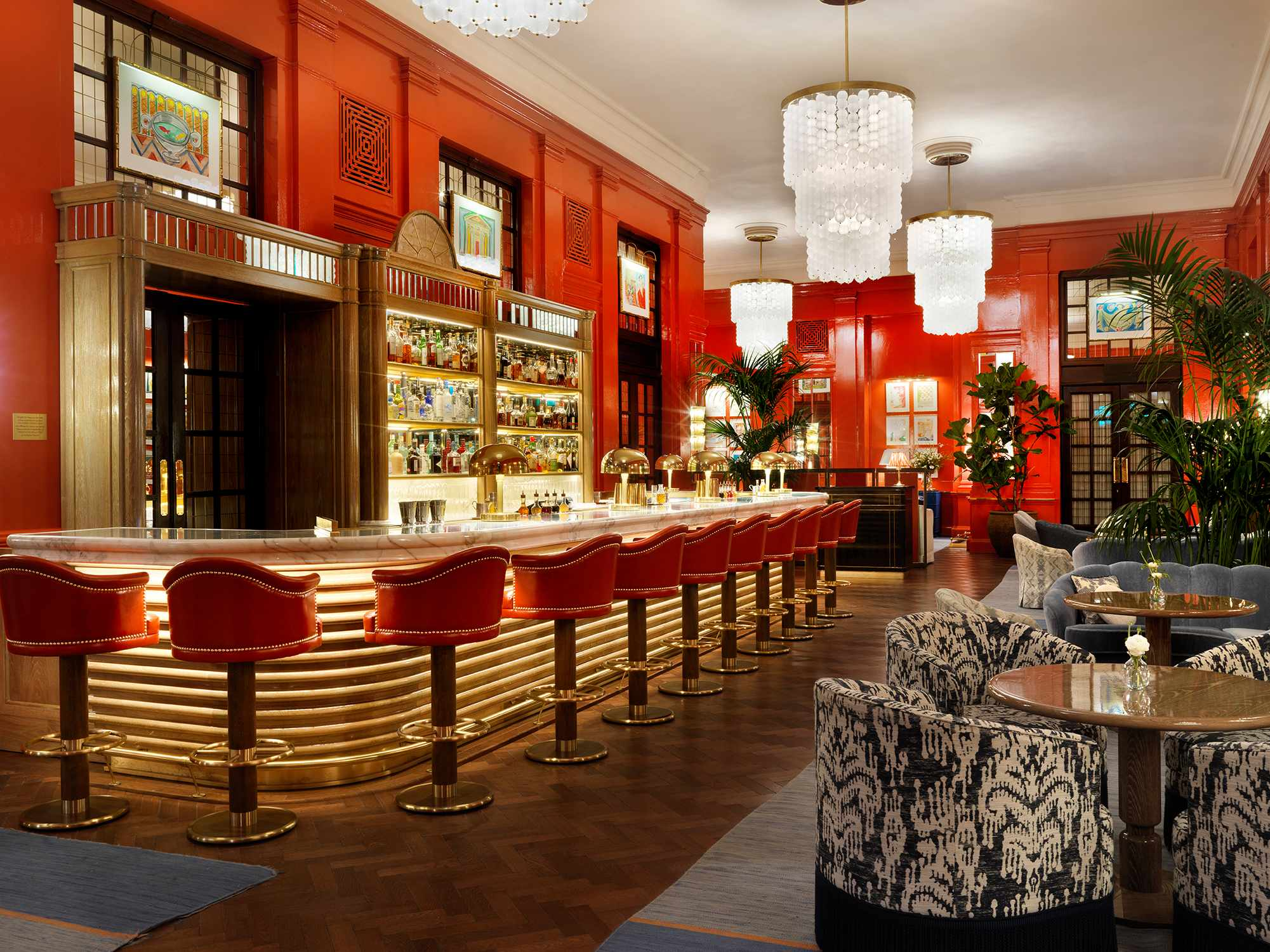 A room with red walls, a bar, tables and chairs