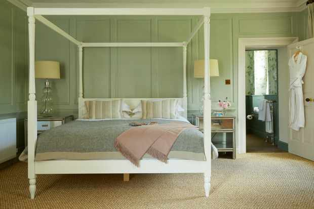 White four poster bed in a light green room Room Six at The Rectory Hotel Crudwell